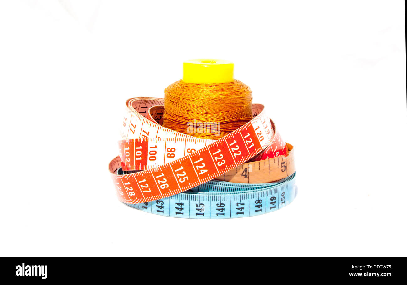 Three tape measures coiled around roll of cotton Stock Photo