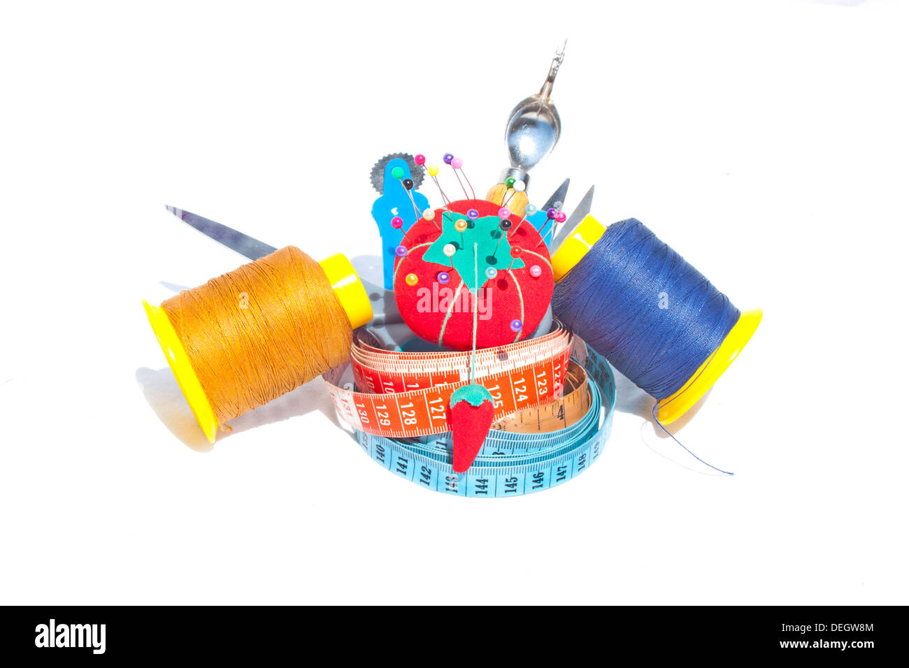 Three measuring tapes with reels of cotton and sewing accessories Stock Photo