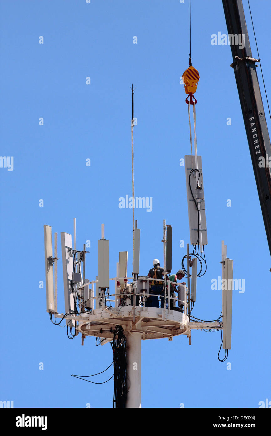 Workmen installing a new mobile phone cell tower array. - Stock Image