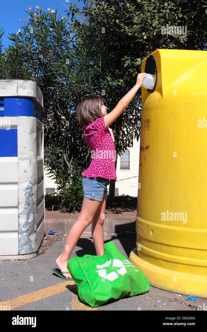a young girl (7-8 years) stretching to put a plastic bottle in the recycling container. - Stock Image