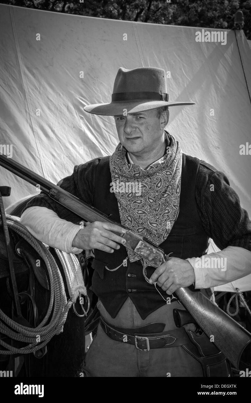 Armed Philip Twaites Cowboy, holding a breech-loading single-shot lever-actuated rifle gun used by the British Army at Ingleton's Wild West Weekend UK - Stock Image