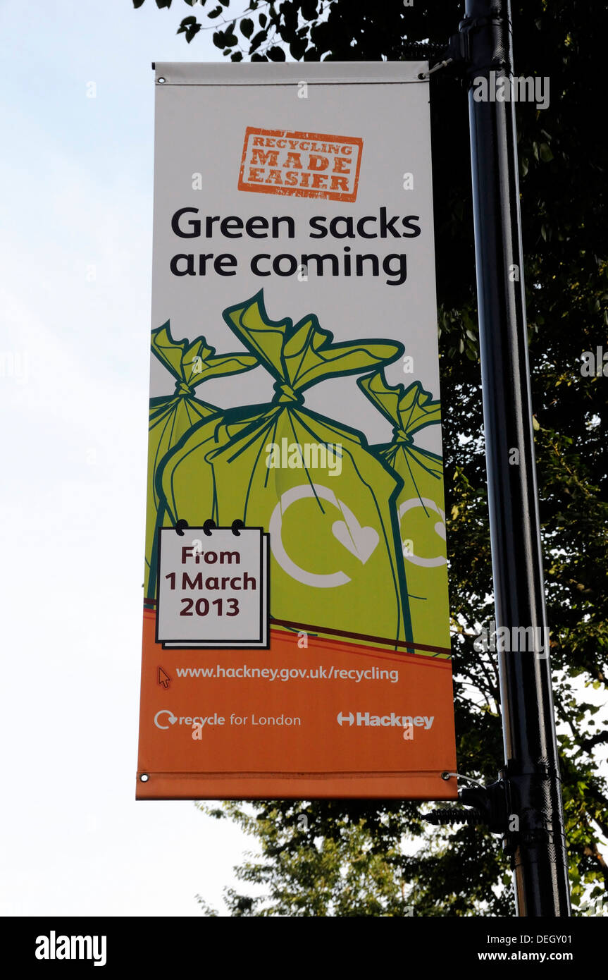 Banner saying Green sacks are coming hanging from lamppost to encourage local residents to recycle their waste Hackney London UK - Stock Image