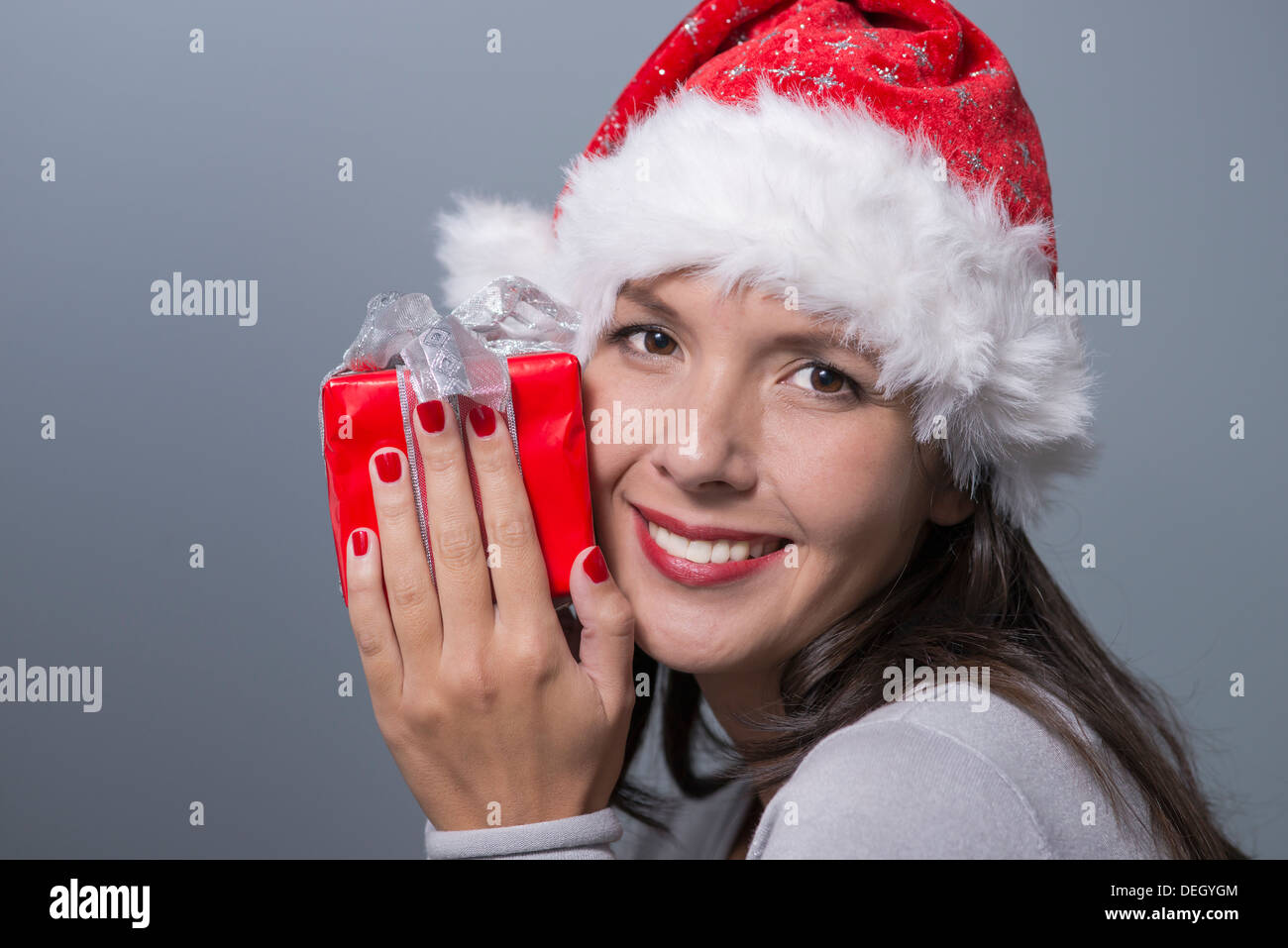 Beautiful woman in a red santa hat - Stock Image