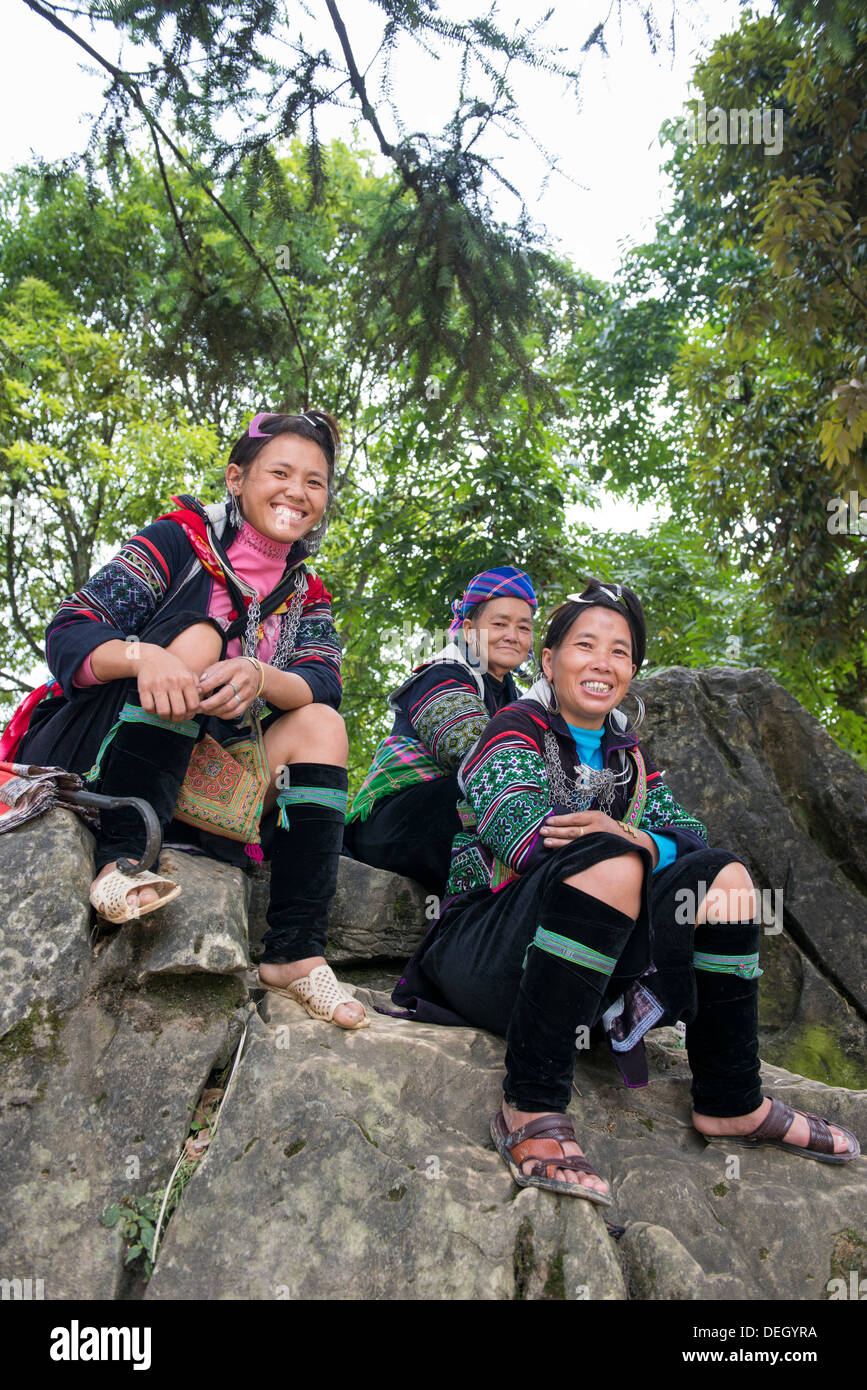 Ethnic group Black Hmong womans sit on the rock in Sa Pa park, Vietnam - Stock Image