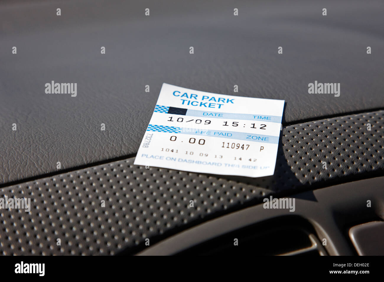 private car park ticket left on show on car dashboard - Stock Image