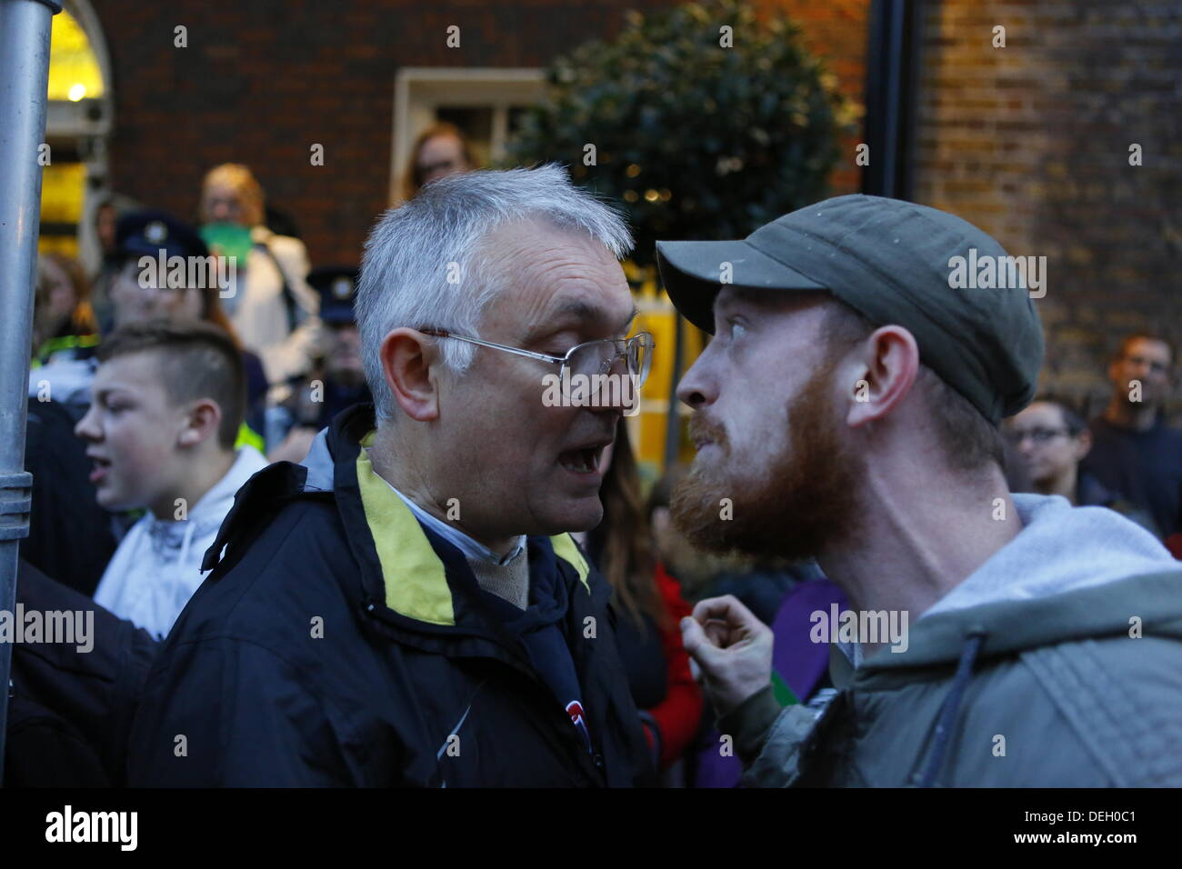 Dublin, Ireland. 18th September 2013. Kieran Allen (L) from the Socialist Workers Party and a protester (R) argue loudly, because the protester was not allowed to speak. Protesters hold a People's Assembly outside the Dail (Irish Parliament), to discuss austerity in smaller groups. The assembly was part of a day of protests to coincide with the return of the TDs (Members of Parliament) from their summer break. Credit:  Michael Debets/Alamy Live News - Stock Image