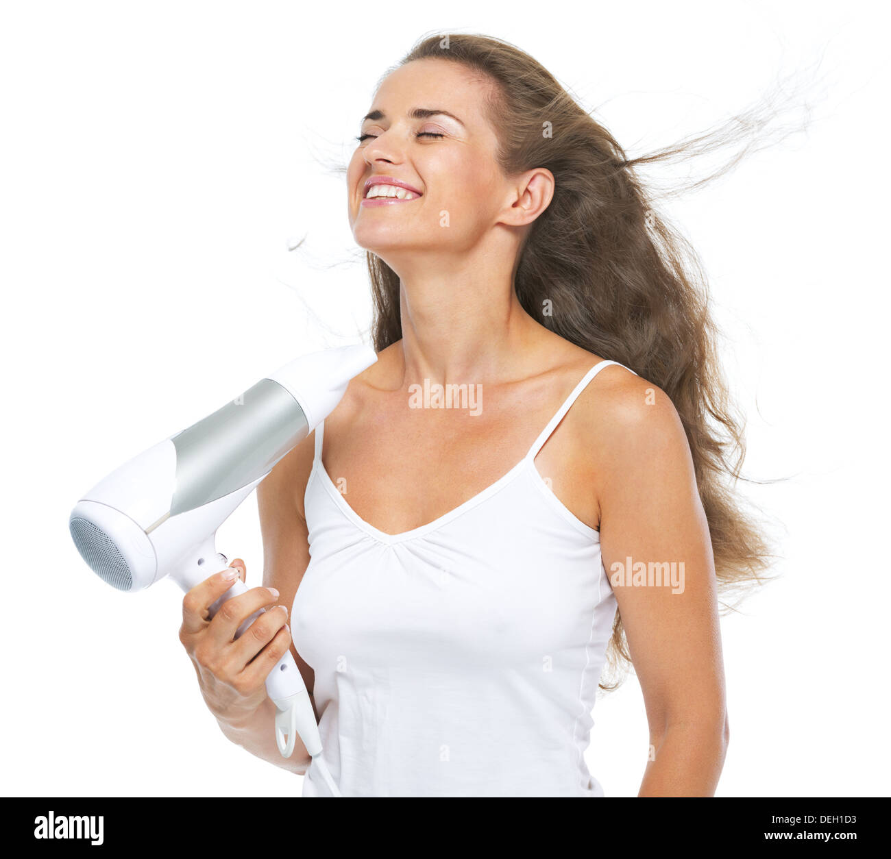 Happy young woman blow-dry - Stock Image