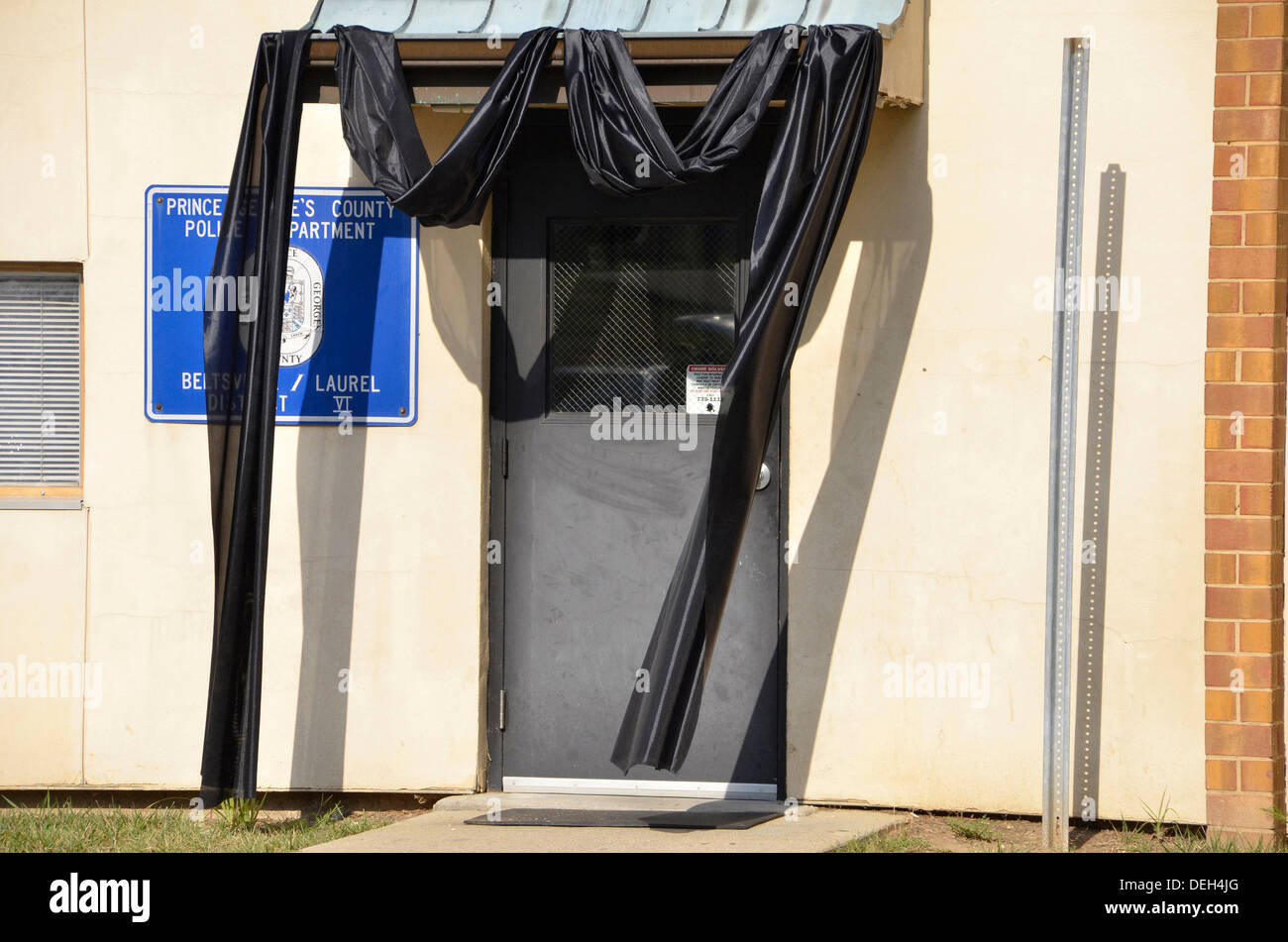 Black drape hangs over  the door of a police station in mourning due to a policeman killed Stock Photo