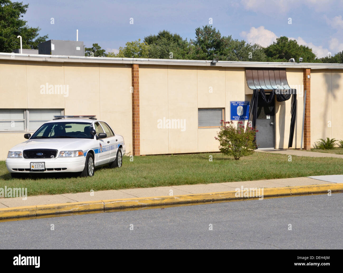 A police car sits in front of a police station draped in black mourning tape for a police officer who was killed - Stock Image