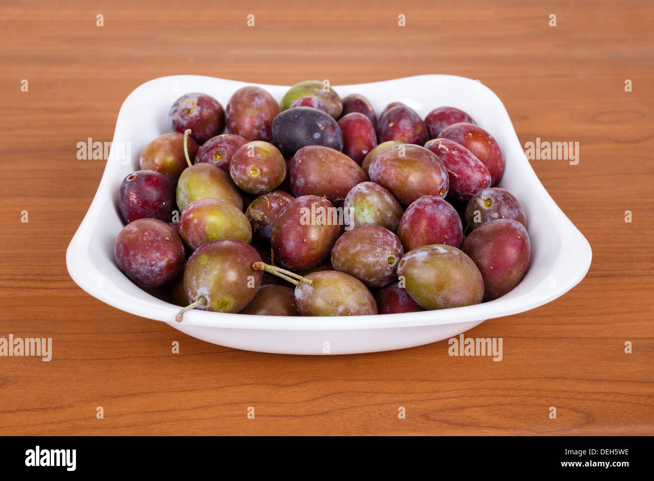 Acid purple and green Plums (Blackthorns) in bowl on wooden desk - Stock Image