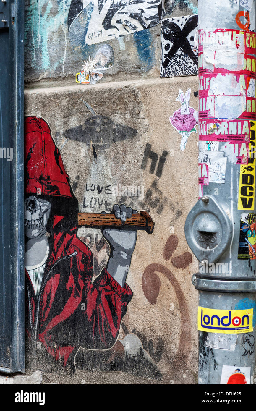 Street art - Skeleton in a red hoody, graffiti and a pipe covered in Stickers - Berlin - Stock Image