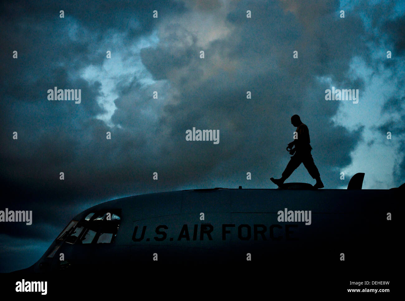A US Air Force crew member walks across the top of a WC-130 Hercules transport aircraft with the 53rd Weather Reconnaissance Squadron during routine maintenance June 5, 2013 in Biloxi, MS. - Stock Image