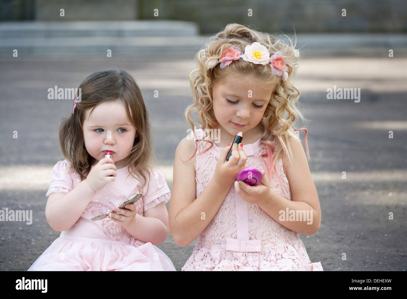 Two preteen girls wearing pink dresses and putting lipstick on. - Stock Image