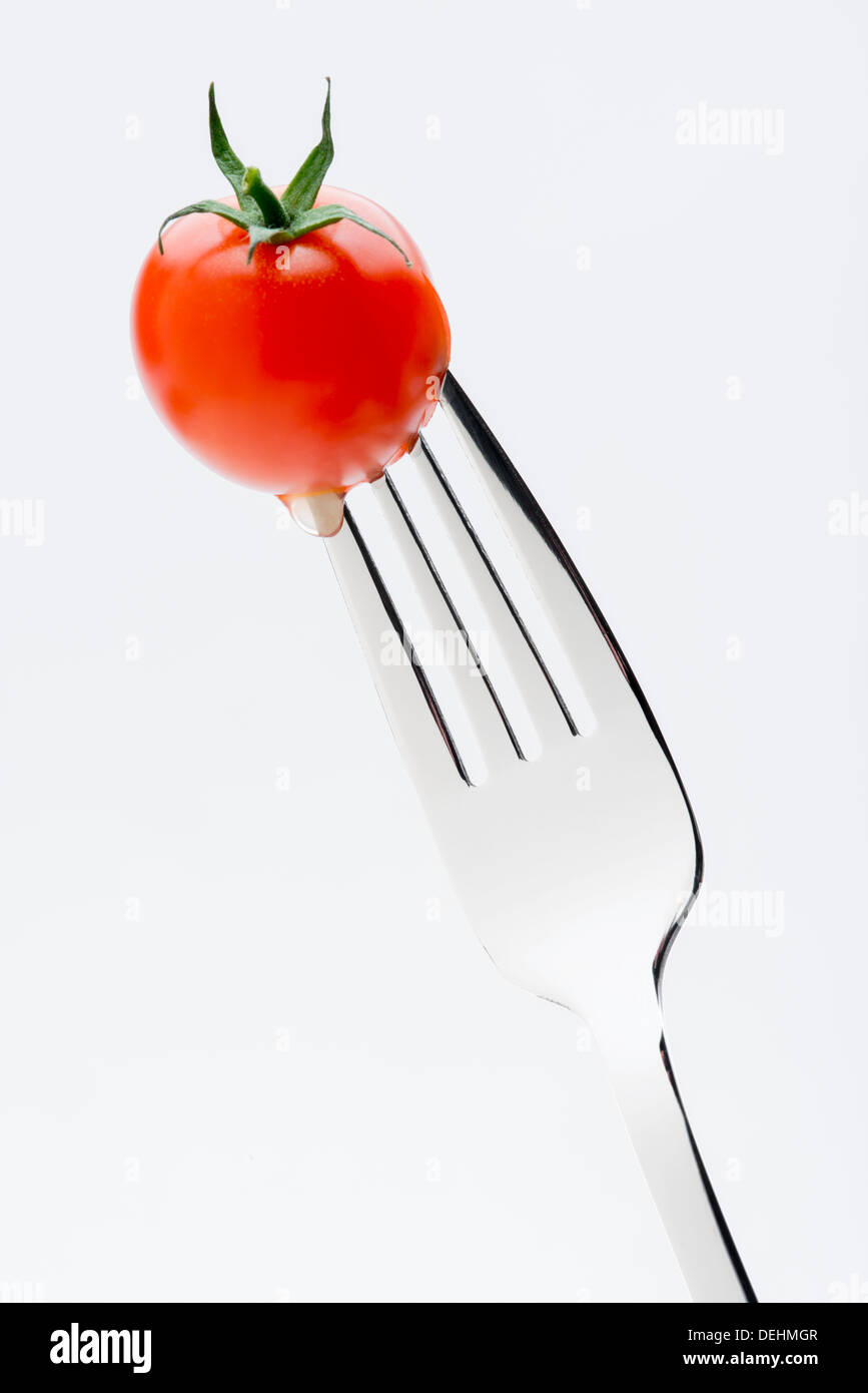 A macro close up of a juicy fresh and tasty cherry tomato stuck on the end of a fork Stock Photo