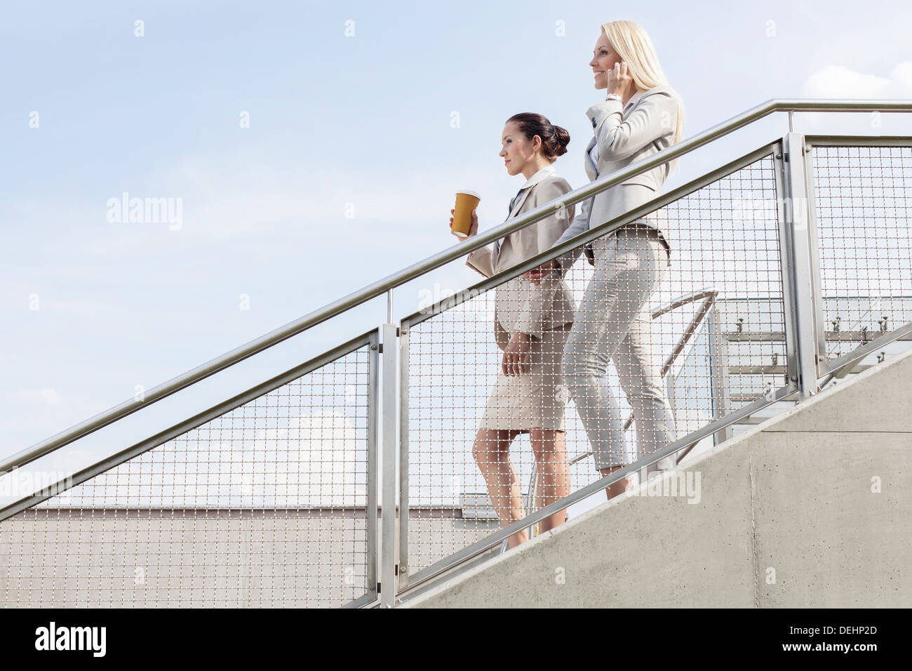 Profile shot businesswomen moving down stairs against sky - Stock Image
