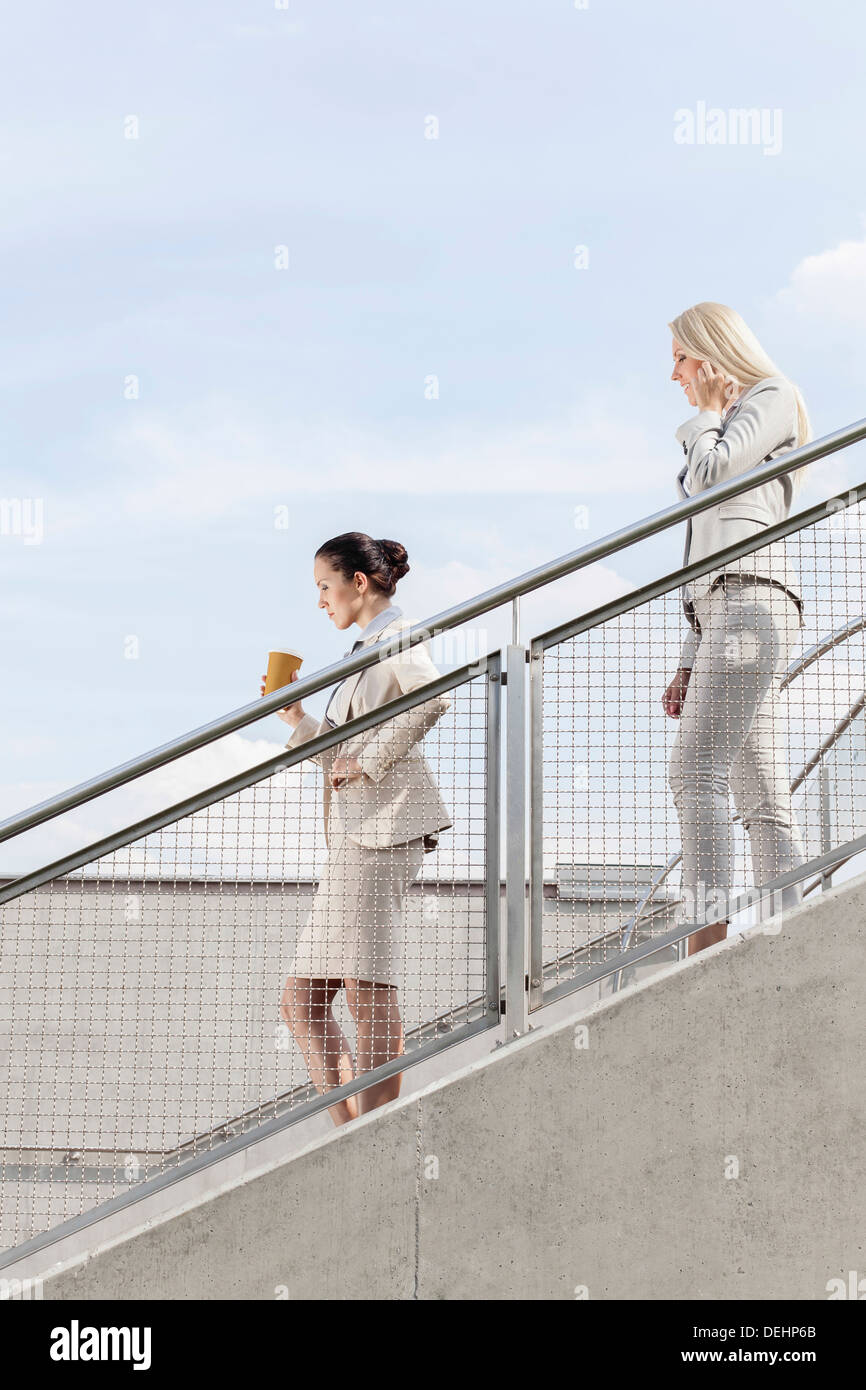 Profile shot businesswomen moving down stairs together against sky - Stock Image