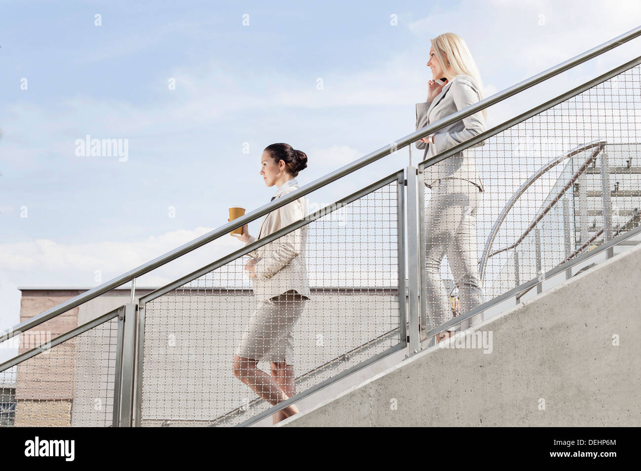 Profile shot businesswomen holding disposable cup mobile phone while moving down stairs together against sky - Stock Image