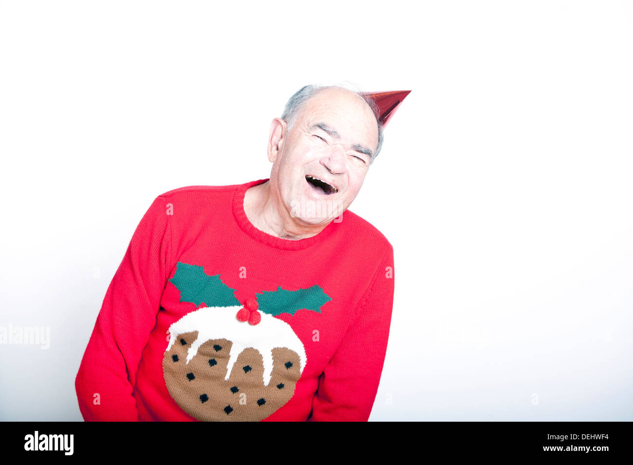 Senior adult man wearing a Christmas jumper a red party hat - Stock Image