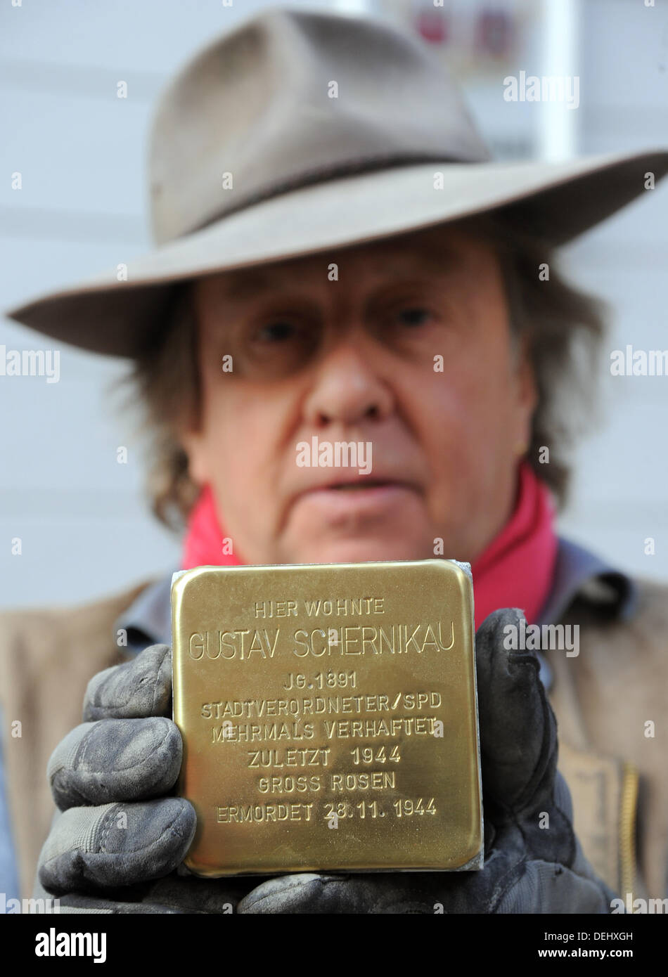 The artist Gunter Demnig holds up the 'Stolperstein' for Gustav Schernikau in Brandenburg an der Havel, Germany, 19 September 2013. Brandenburg an der Havel is the 892nd city that installs these memorial stones in front of victims of the NS-Regime in front of their last domiciles. Photo: BERND SETTNIK - Stock Image
