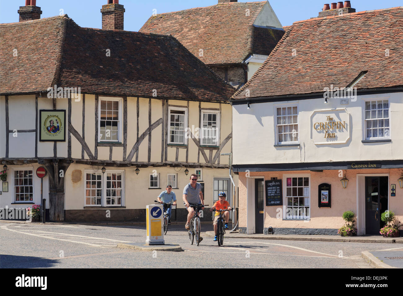 People cycling past 15th century Admiral Owen pub and 16th century Crispin Inn in historic Cinque Port town of Sandwich, Kent, England, UK, Britain - Stock Image