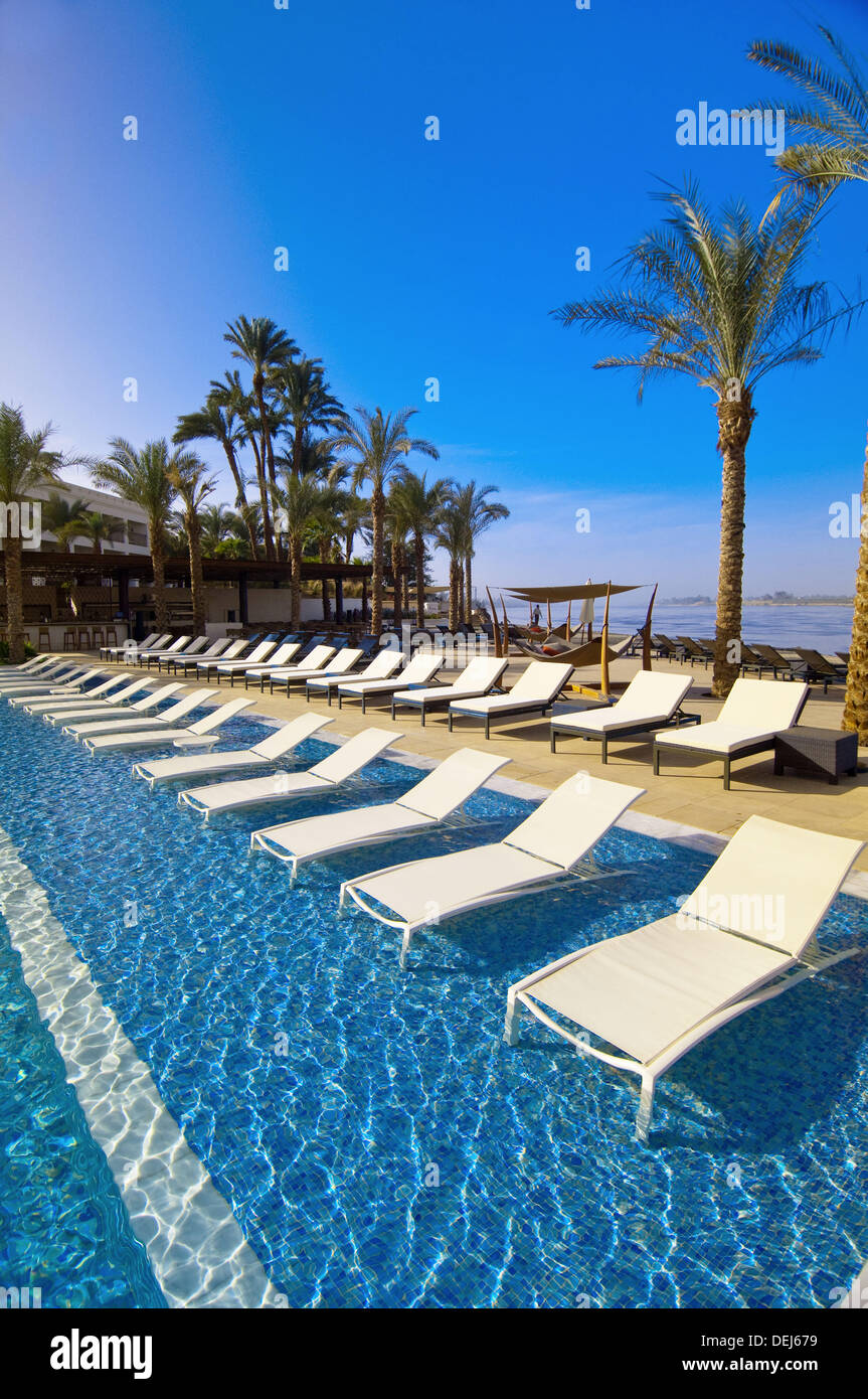 Submerged pool loungers, Hilton Luxor Resort and Spa, on the Nile River, Luxor, Egypt - Stock Image