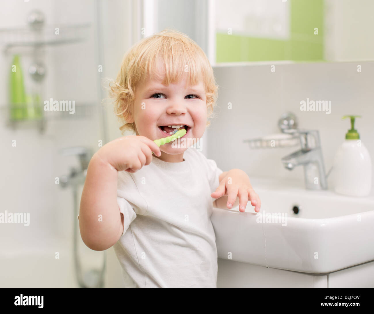 Happy kid brushing teeth - Stock Image