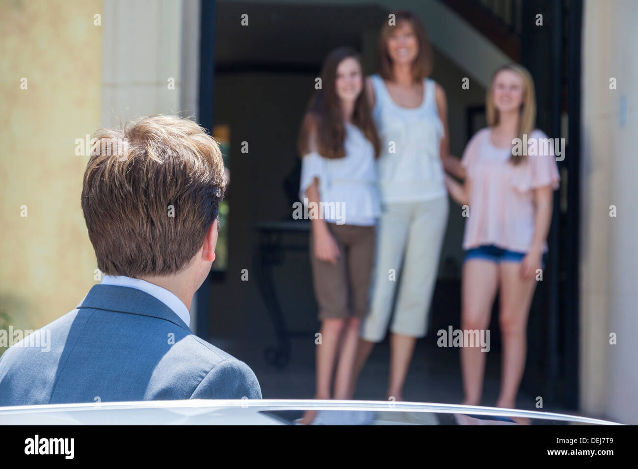 A father & husband arriving home from work to see his family of wife and two daughters - Stock Image