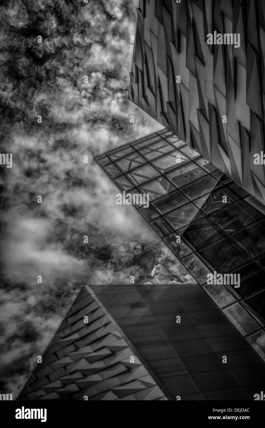 Low, angled black and white of a modern architecture building with stormy clouds above - Stock Image