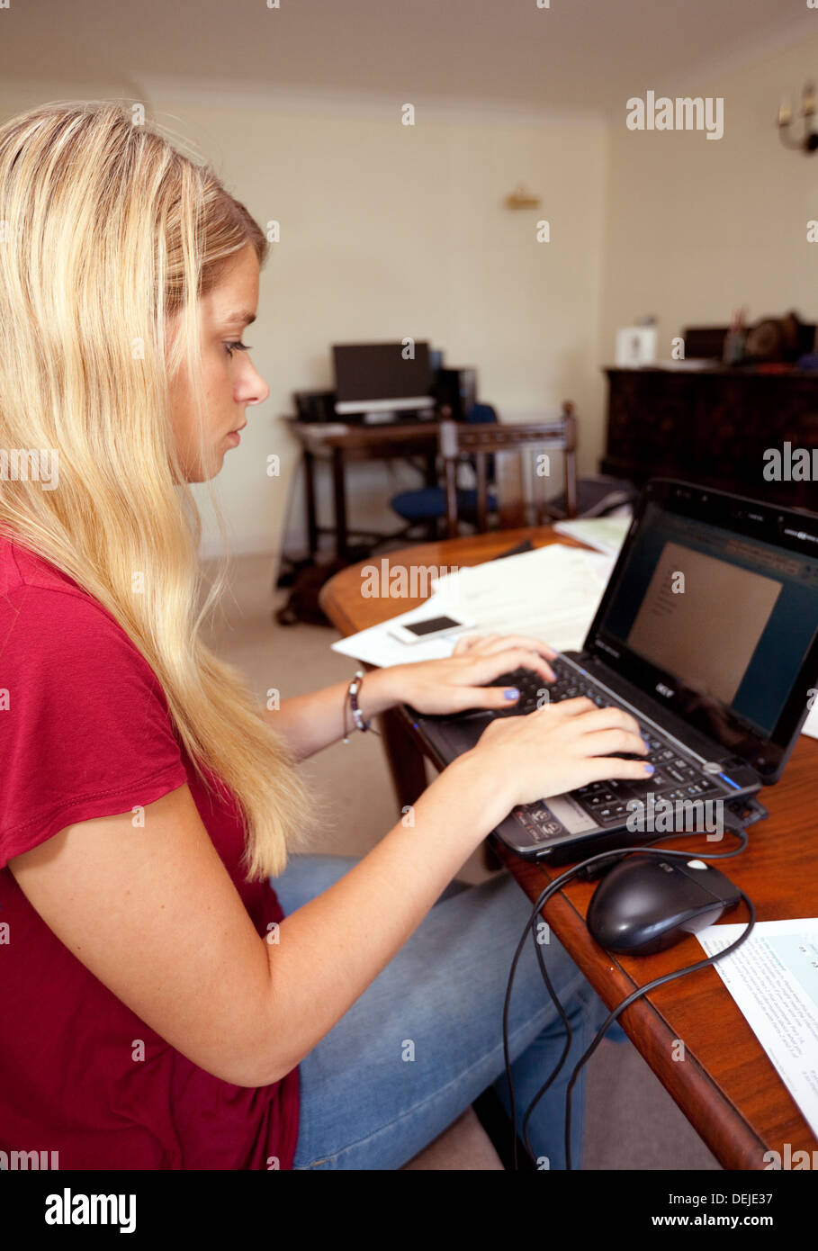 Young woman sitting at a table working on a laptop computer doing paperwork at home, UK - Stock Image
