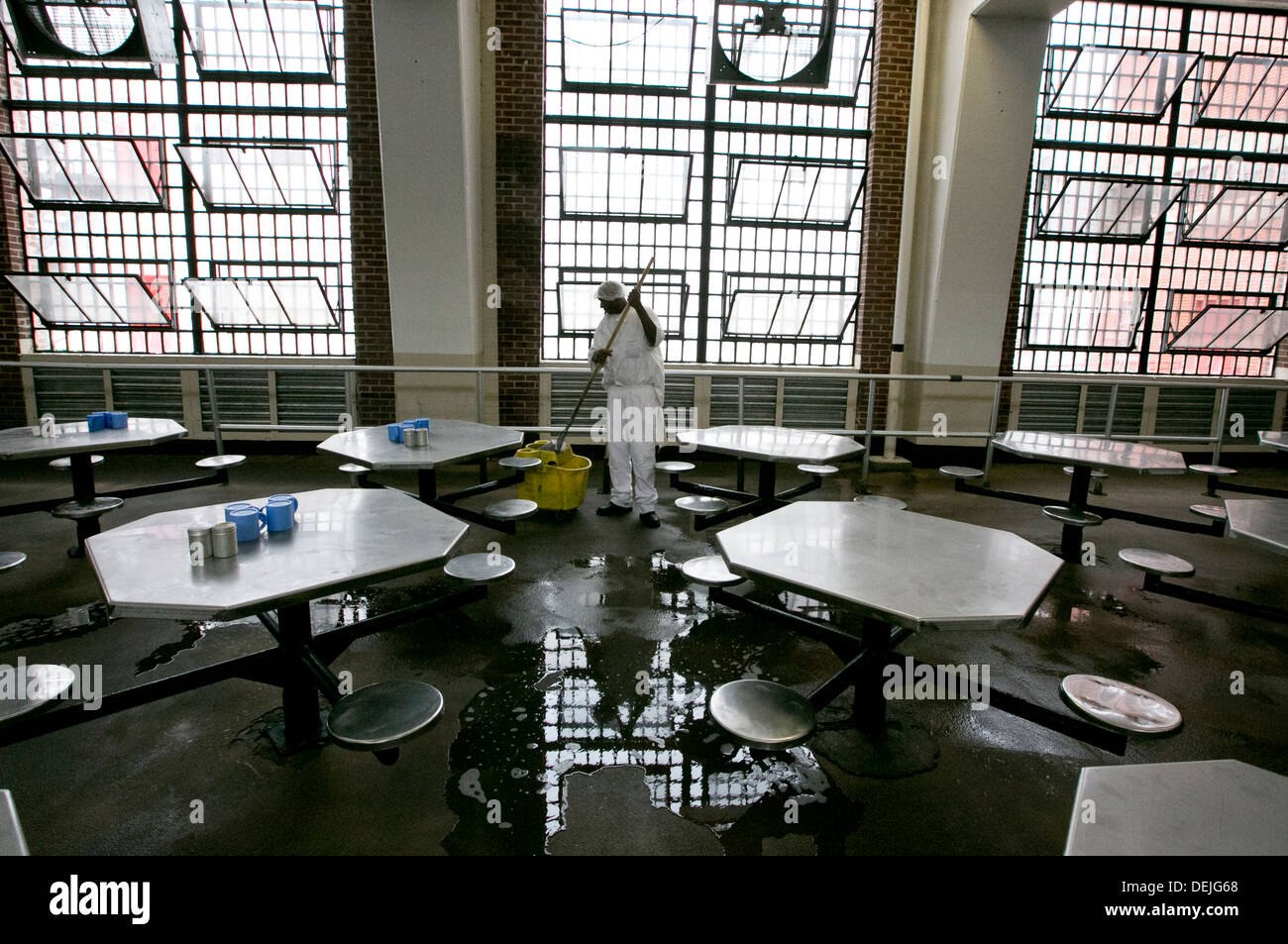 Male inmate works mopping up the floor in cafeteria dinning area inside maximum security prison near Houston, Texas - Stock Image