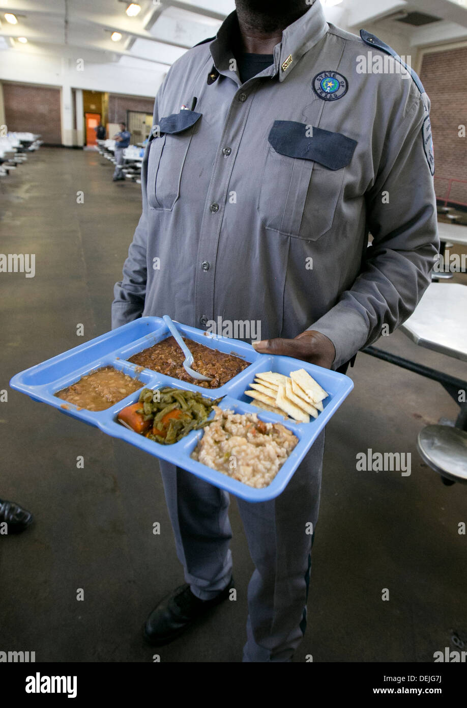 A Prison Security Guard Hold Up A Tray With Food Choice