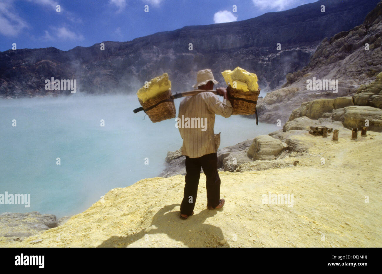 Miner with heavy load of yellow elemental sulphur collected from within the active crater of Volcano Ijen, eastern Java, - Stock Image