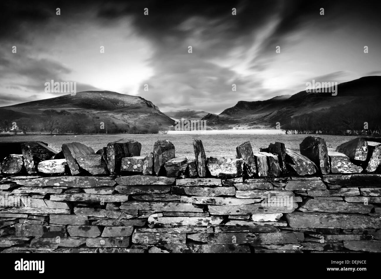 Stone wall and sunset in North Wales, UK, summit of Snowdonia in background Stock Photo