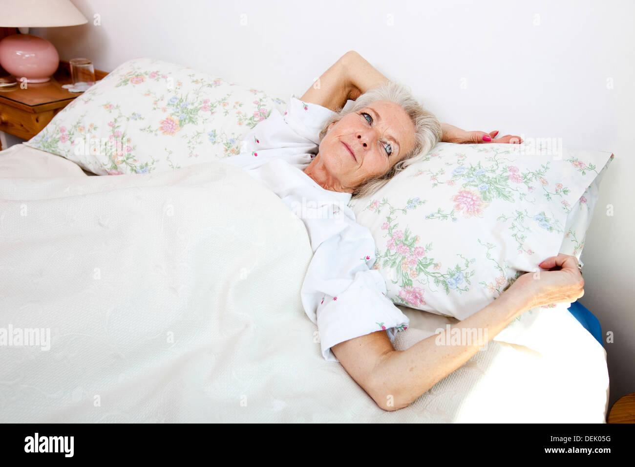 High angle view senior woman looking away while lying bed home - Stock Image