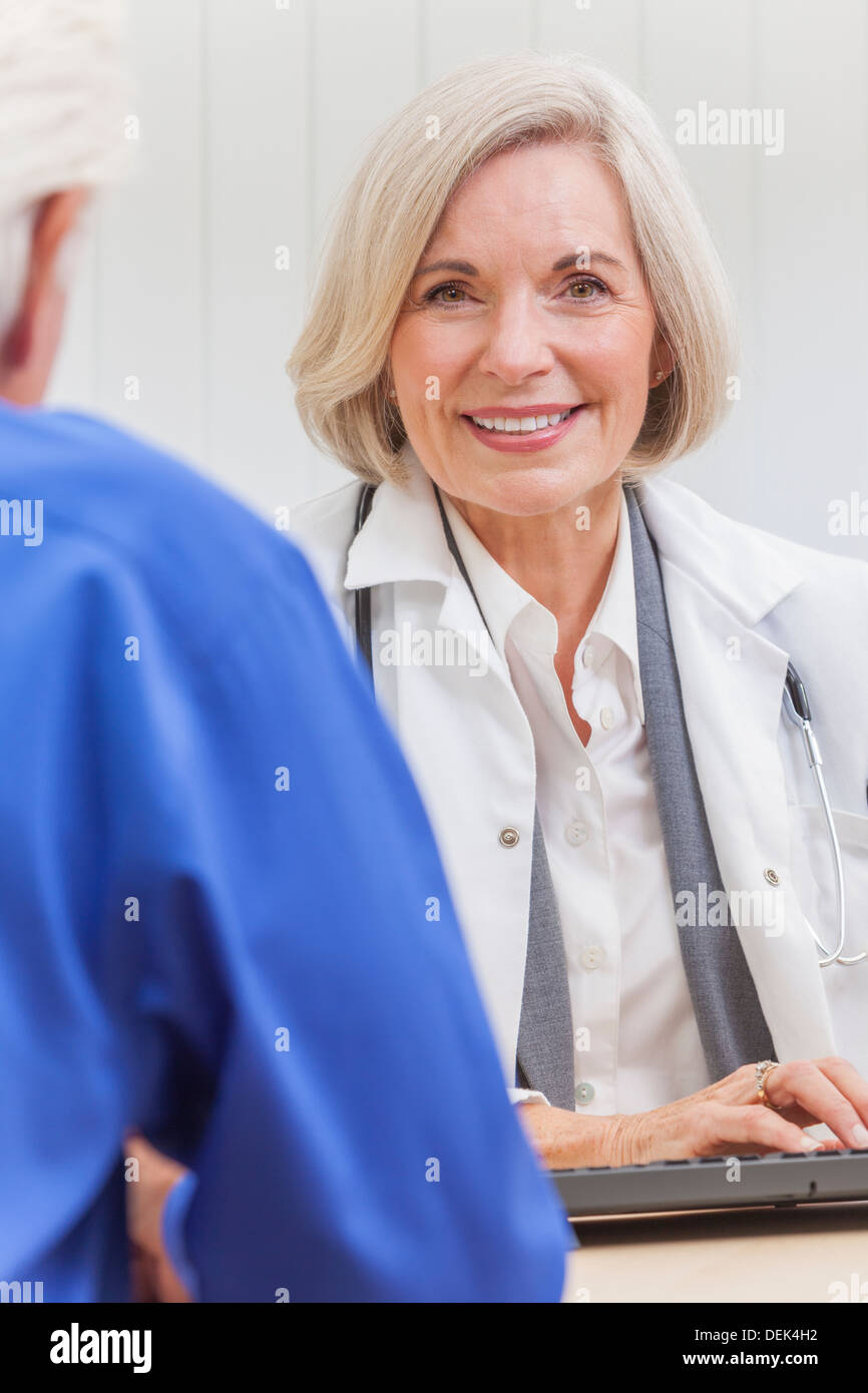 A senior female woman doctor sitting at a desk wearing a suit and stethoscope talking to an elderly male patient - Stock Image