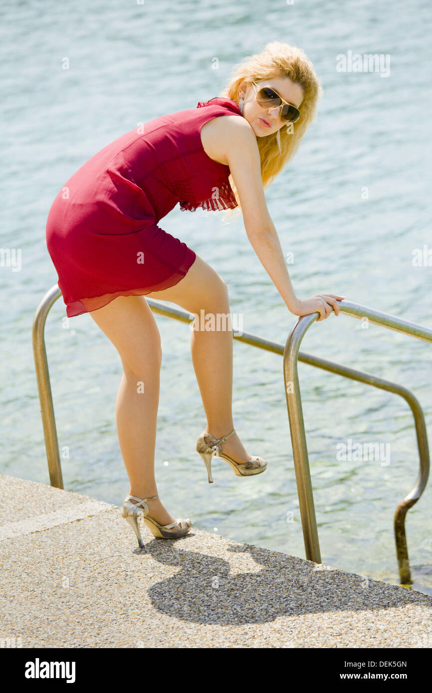 Pretty blonde woman in Red miniskirt and high heels is going to enter water - Stock Image