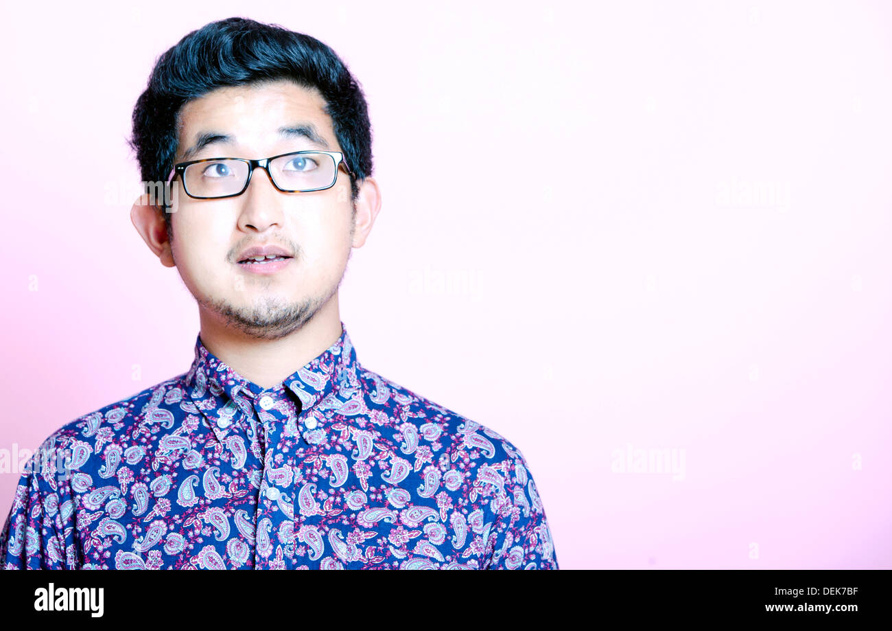 Young Geeky Asian Man colorful shirt wearing glasses - Stock Image
