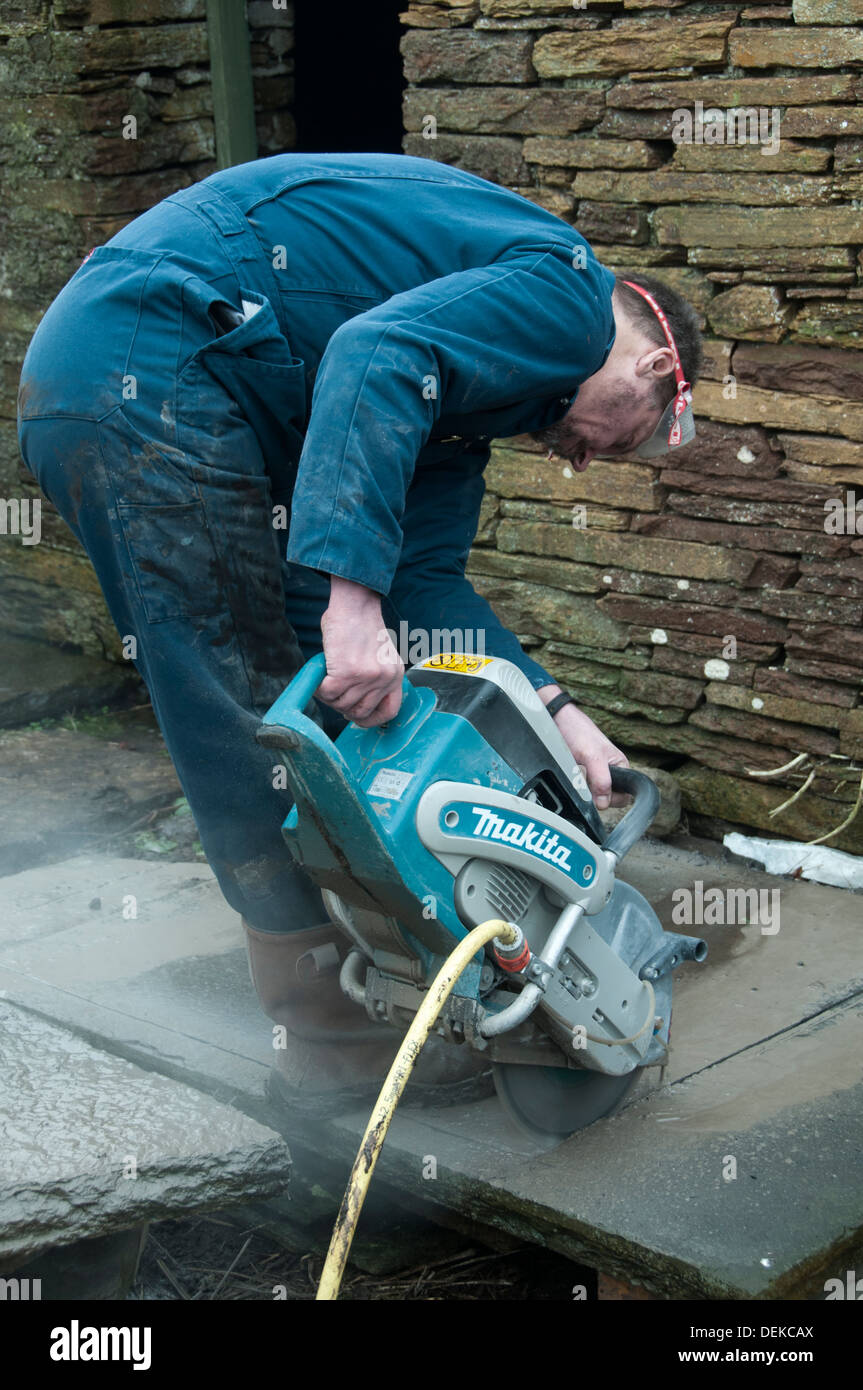 Workman using an industrial circular saw with a diamond blade to cut a slab of sandstone. - Stock Image