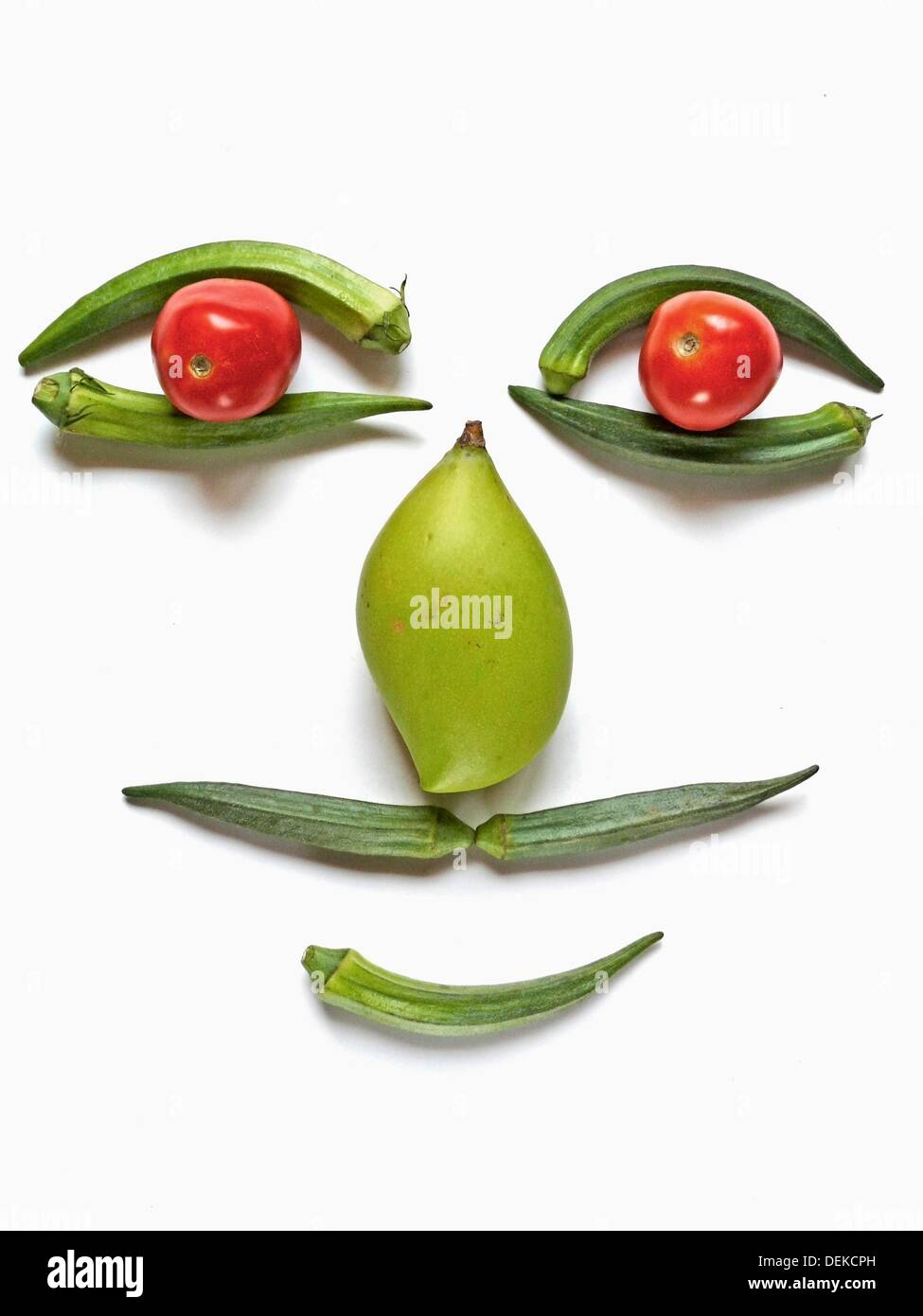 Amusing face made from vegetables Lady finger, tomatos and a mango are arranged in human face like shape Pune, Maharashtra, - Stock Image