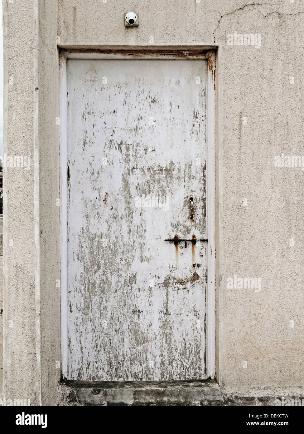 A rotten, decomposed flush door because of rainwater is on a terrace of a residential building. Pune, Maharashtra, India. - Stock Image