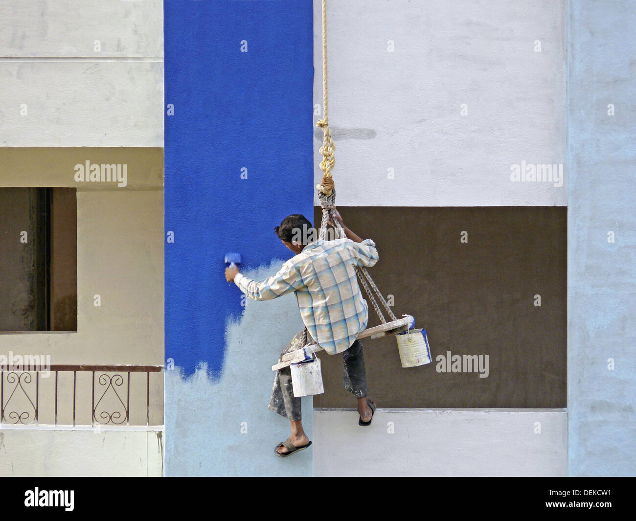 A Painter is seating on a cradle and working on a buildings