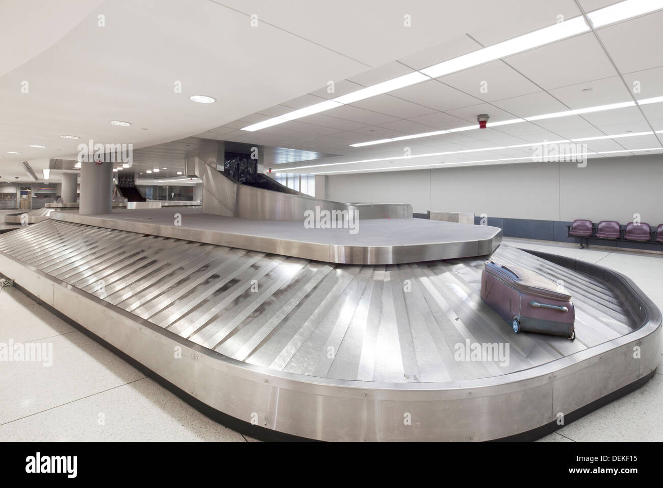 Suitcase on baggage claim carousel in airport - Stock Image