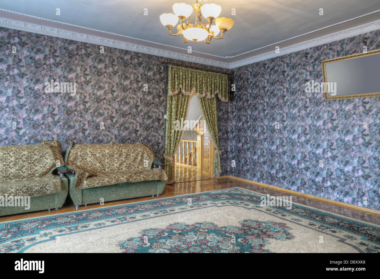 Wallpaper, sofa and drapes in ornate room - Stock Image