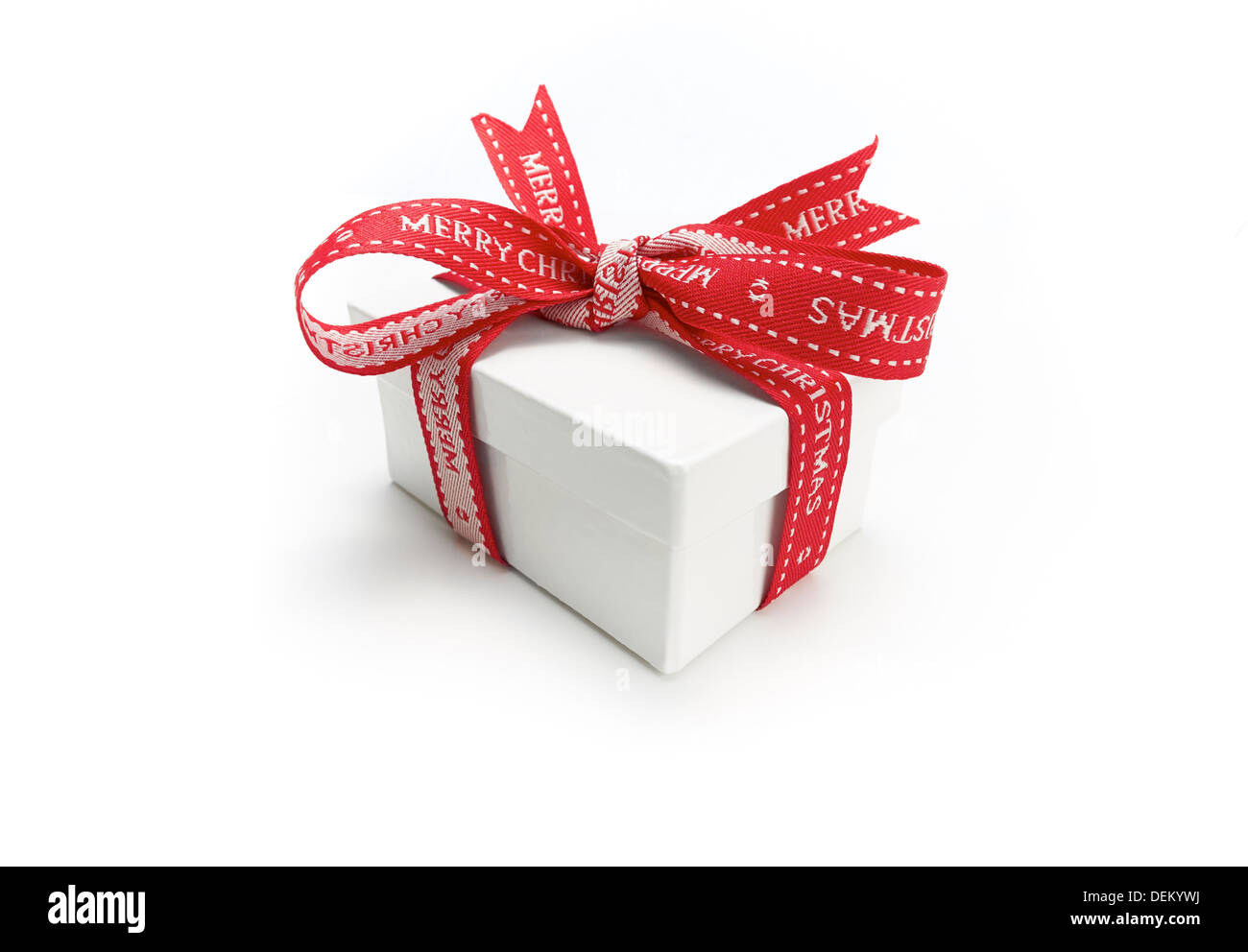 A wrapped Christmas present with a colourful red ribbon bow on a white background. Stock Photo