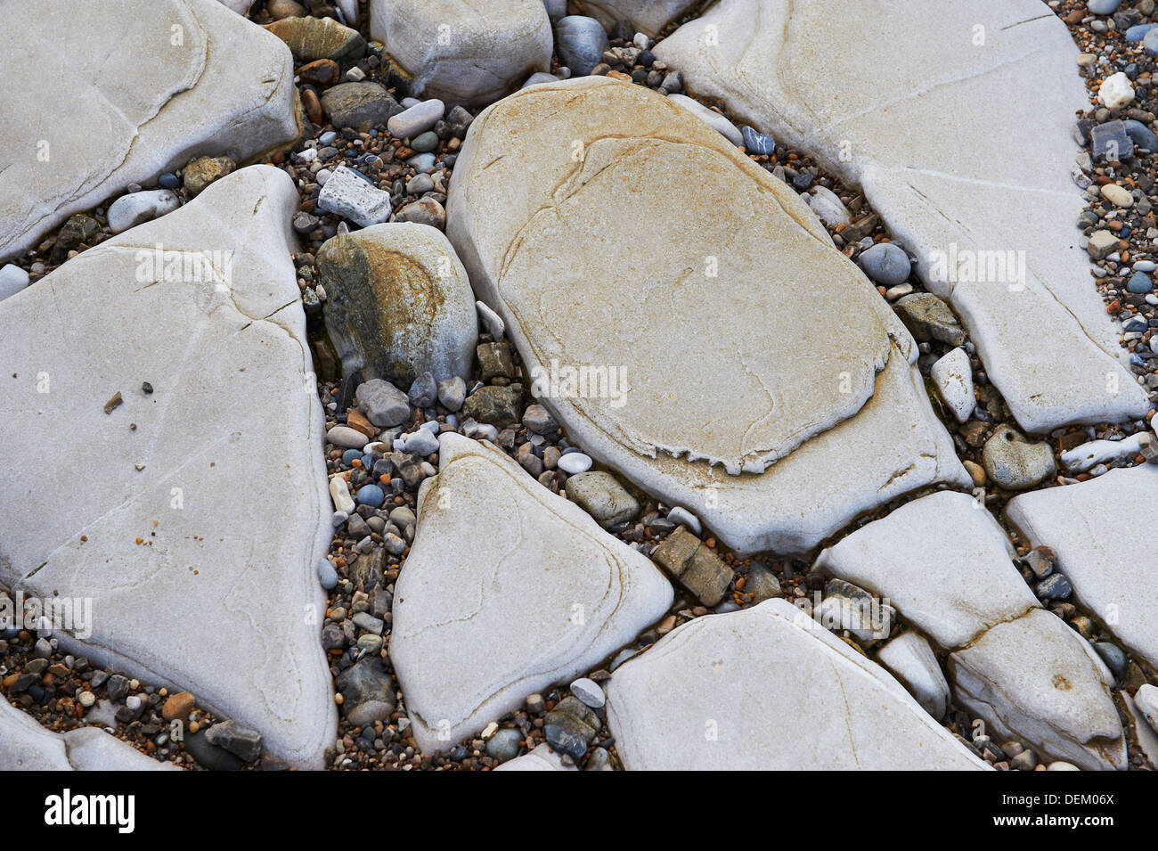 natural patterns formed by rocks and pebbles on a beach - Stock Image