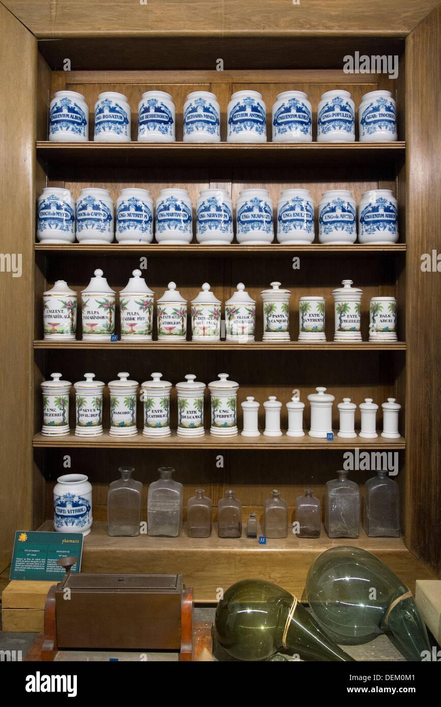 jugs bottles old antique pharmacy shelves - Stock Image