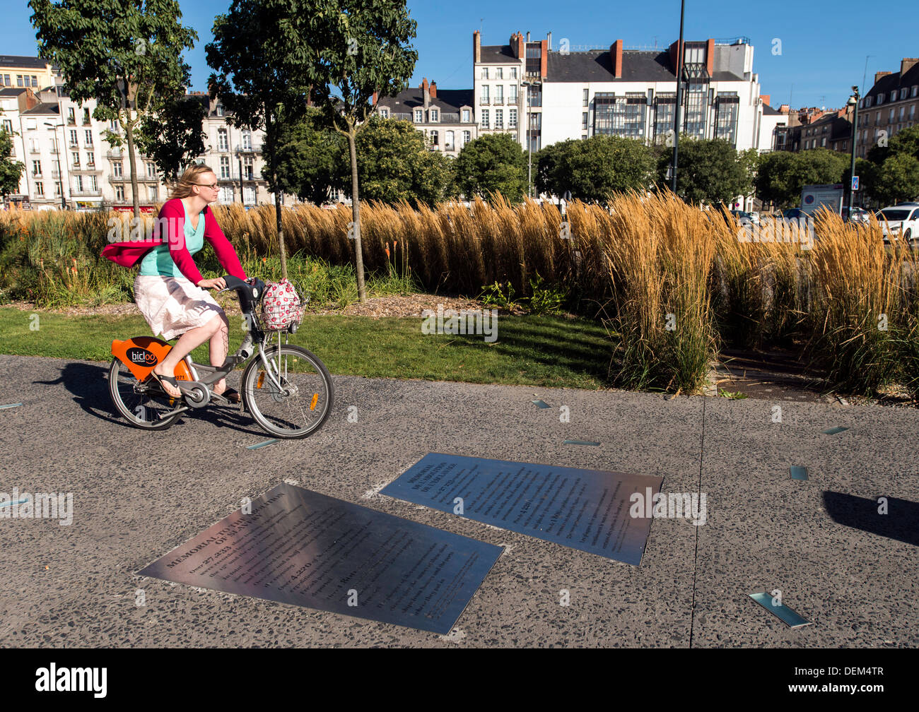 Cyclist by Memo­r­ial to the Abo­li­tion of Slavery Nantes France - Stock Image