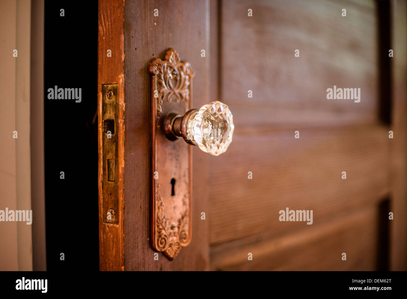 Closeup of an antique wooden door in the interior of a home with a glass doorknob and skeleton key hole. & Closeup of an antique wooden door in the interior of a home with a ...