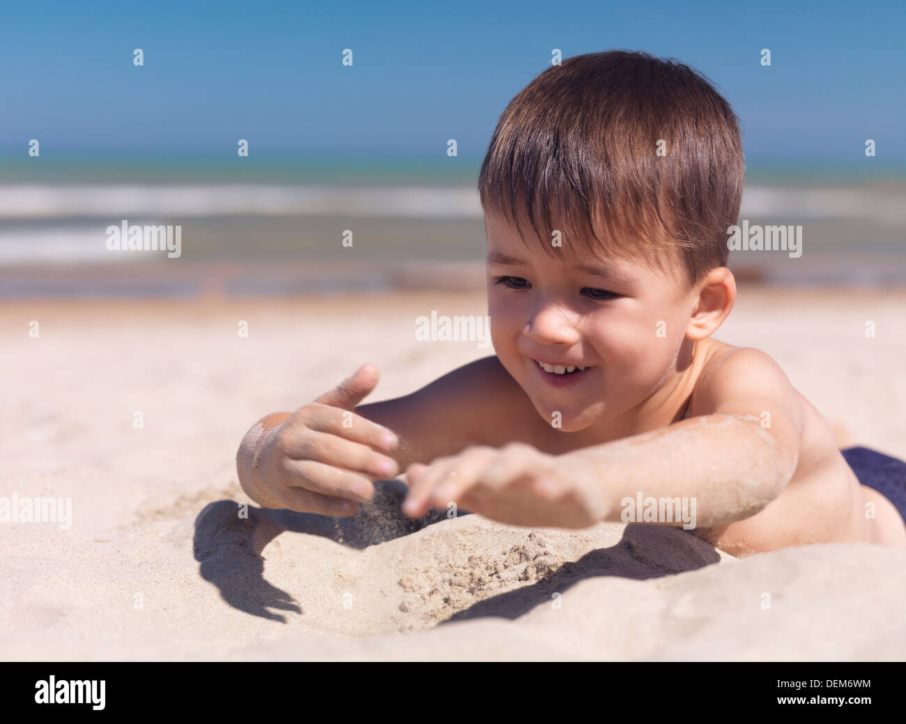 Happy smiling cute little boy playing with sand at the beach. Three year old child. Lake Huron, Ontario, Canada. - Stock Image