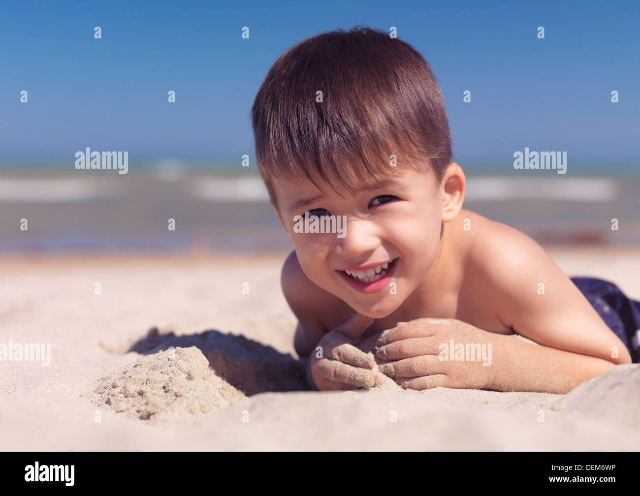 Portrait of a cute happy child playing in the sand on the beach. Lake Huron, Ontario, Canada. - Stock Image